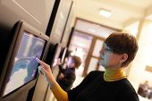 pic of realism  - Woman using touch screen in a museum - JPG