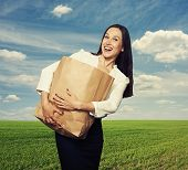 stock photo of heavy bag  - laughing woman holding heavy paper bag at outdoor - JPG