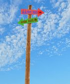 stock photo of nudism  - wooden arrow direction signs post to the nude female and male beach against a blue sky - JPG
