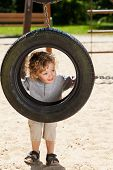 stock photo of tire swing  - Cute little boy looking through tire swing - JPG