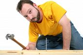 picture of f18  - Man in yellow shirt and jeans hammering in a nail - JPG