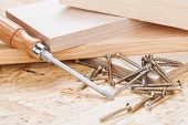 foto of joinery  - Close up view of a Phillips head screwdriver and threaded metal wood screws with one screw inserted into a plank of wood in a carpentry joinery and construction concept - JPG