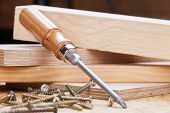 pic of joinery  - Close up view of a Phillips head screwdriver and threaded metal wood screws with one screw inserted into a plank of wood in a carpentry joinery and construction concept - JPG