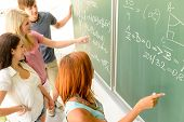 pic of classmates  - Math lesson student write on green chalkboard with classmates pointing - JPG