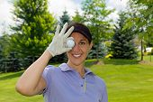 image of ladies golf  - Woman golfer holding a golf ball over her eye
