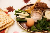 stock photo of matzah  - plate for the Seder Matzah horseradish a hard-boiled egg parsley a mixture of crushed nuts chopped fruit spices and wine Haroset Salted water bone Symbols of the feast laid on the plate for the Seder white background isolated
