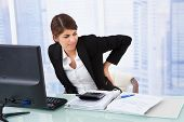 pic of suffering  - Tired young businesswoman suffering from backache sitting at computer desk in office - JPG