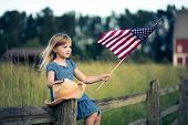 foto of country girl  - Little girl with American flag sitting on the fence.
