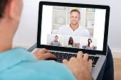 picture of video chat  - Man having video conference with friends on laptop at home - JPG