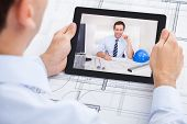 picture of video chat  - Cropped image of male architect video conferencing with colleague through digital tablet in office - JPG