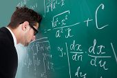 picture of professor  - Side view of sad young male professor leaning head on blackboard in classroom - JPG