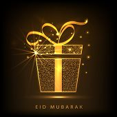 stock photo of eid festival celebration  - Shiny golden gift box with ribbon on brown background for muslim community festival Eid Mubarak celebrations - JPG
