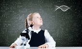 stock photo of microscopes  - Cute school girl with microscope against blackboard with formulas - JPG