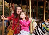 foto of merry-go-round  - a young mother and her daughter riding on a merry go round at t - JPG