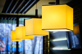 stock photo of lamp shade  - Modern restaurant interior with yellow square lamps - JPG
