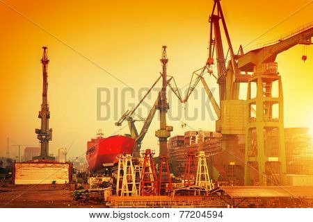 Cranes in historical shipyard in Gdansk, Poland at sunset. Heavy machinery in harbour on the Baltic sea.