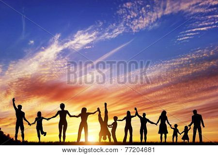 Happy group of diverse people, friends, family, team standing together holding hands and celebrating success. Sunset sky