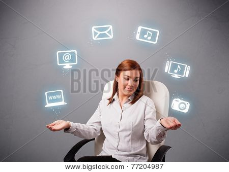pretty girl sitting and juggling with elecrtonic devices icons