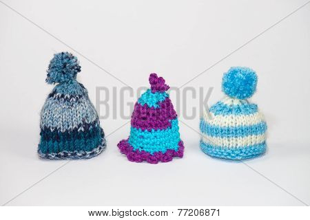 Three little knitted bobble caps