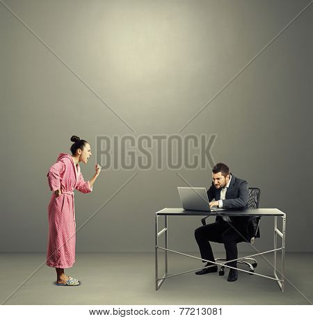 angry woman screaming at busy husband over grey background