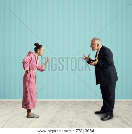 angry housewife screaming at senior man in formal wear in the room