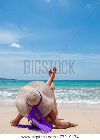 A sexy young woman or girl wearing a bikini and sun hat sitting on a deserted tropical beach in Bali