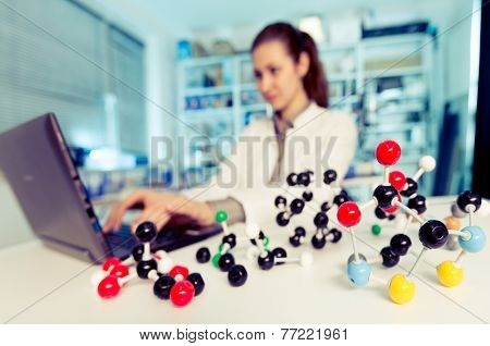 A woman laboratory assistant uses a computer  for the simulation of organic molecules