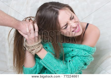 Man hitting a young woman.  hands are tied