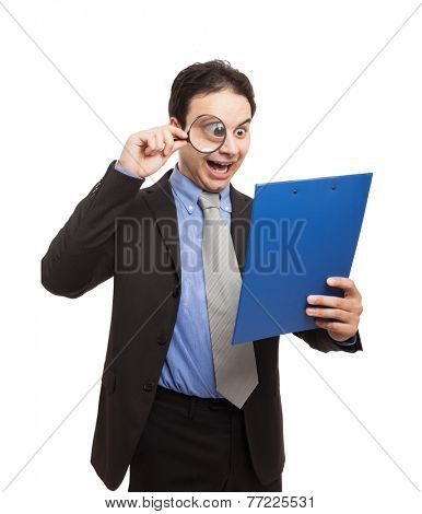 Shocked businessman reading a document using a magnifying glass. Isolated on white