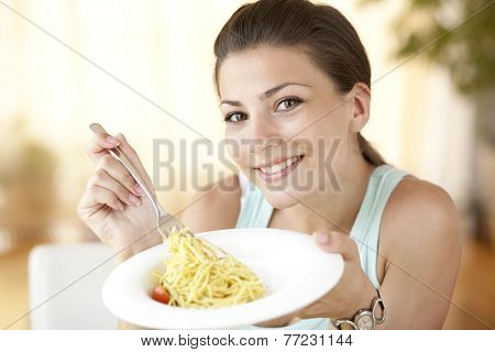 Young beautiful woman eating italian pasta with tomatoes, parmezan and basil
