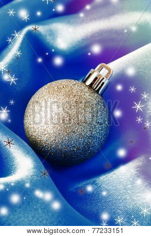Beautiful Christmas ball on blue satin cloth