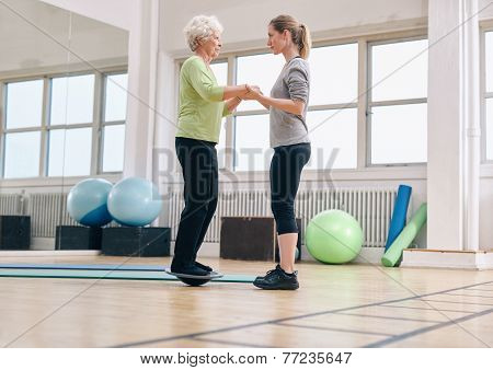 Trainer Helping Senior Woman Exercising With A Bosu Balance