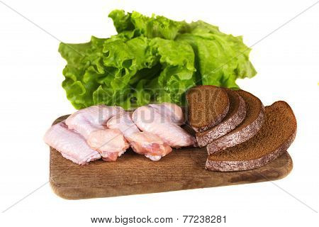Raw Chicken Pieces With Black Bread On The Kitchen Blackboard