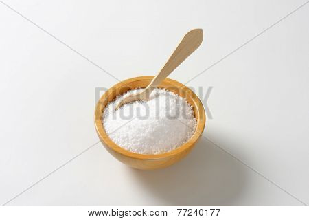 wooden bowl with salt and immersed wooden teaspoon
