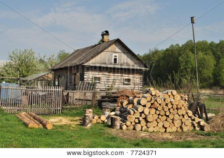 Country House With Pile Of Firewood
