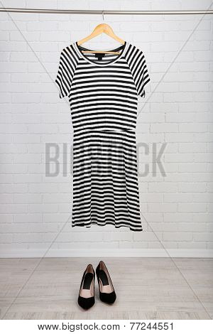 Female dress on hanger and shoes in room
