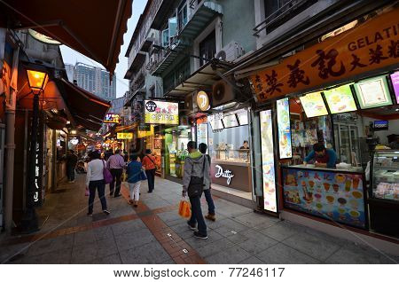 Tourists and locals walk in narrow old city street in Macau.