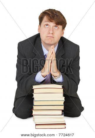 Student betet vor der Untersuchung auf Haufen von Lehrbüchern