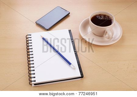desk with stationery phone and cup of coffee
