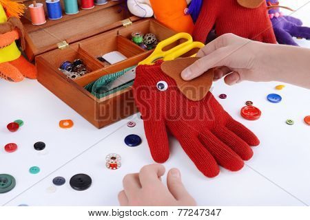 Making of handmade toys from gloves on white background