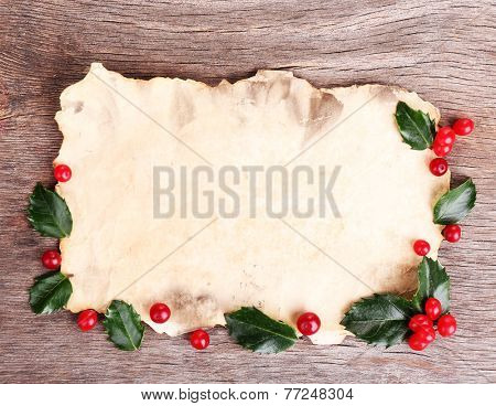 Empty paper with European Holly (Ilex aquifolium) with berries on wooden background