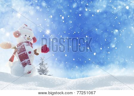 Happy snowman standing in winter christmas landscape
