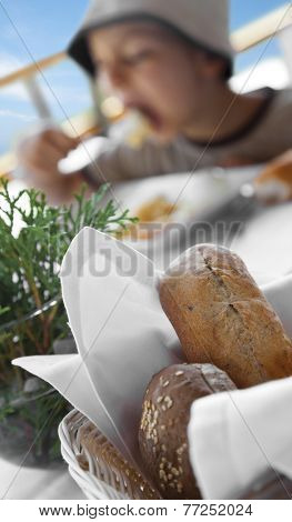 Fresh bread in front of an eating blurred in the background boy.
