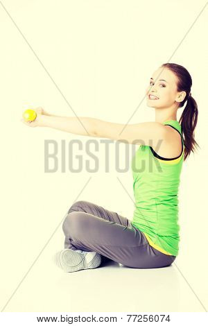 Attractive young woman sittinh and holding free weights. Isolated on white.