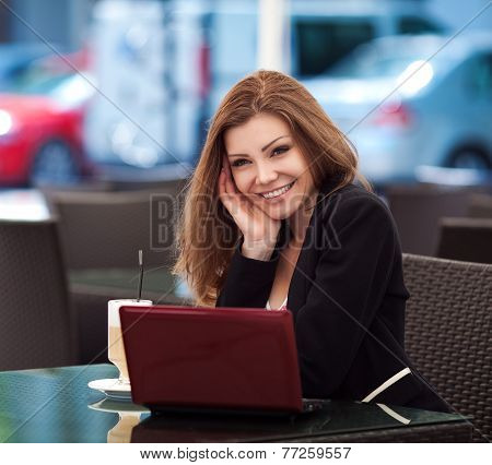 Business woman drinking morning coffee in a city cafe.