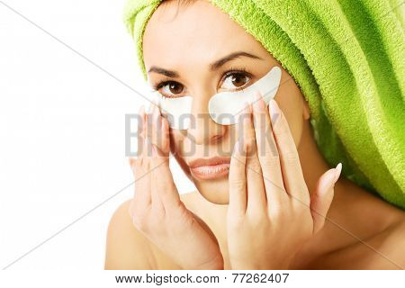 Caucasian woman with gel eye mask touching face.