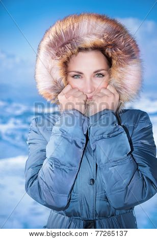 Closeup portrait of cute female outdoors in winter time, wearing stylish casual blue coat with furry hood, winter fashion concept