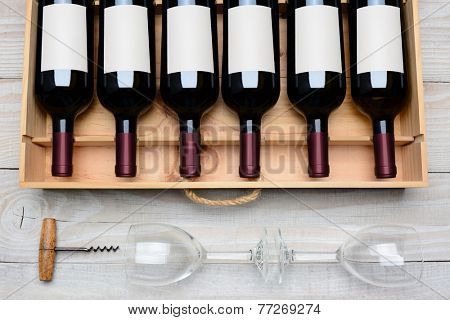 Overhead shot of a case of red wine bottles with blank labels  on a rustic white wood table with wine glasses and cork screw below. Horizontal format.