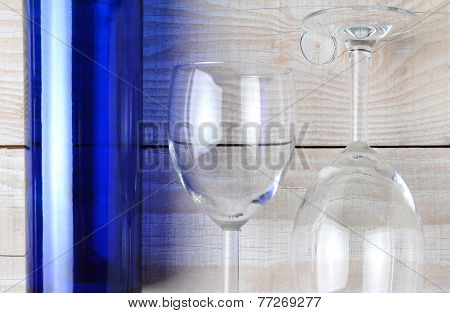 High angle shot of a blue wine bottle and two wine glasses on a rustic white wood table. Horizontal format.