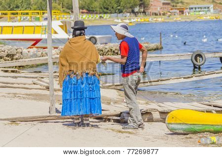 COPACABANA, BOLIVIA, MAY 7, 2014: Local woman in traditional attire talks to young man in port (Titicaca lake)